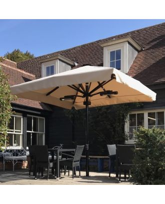 heated parasol with black frame and beige canopy opened over terrace with 2 tables next to a pub